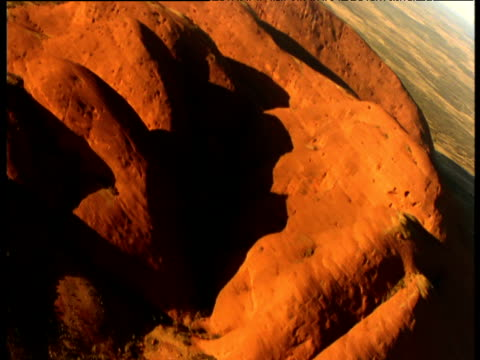 sweeping track over glowing red sandstone olgas rising out of outback, northern territory, australia - sandstone stock videos & royalty-free footage