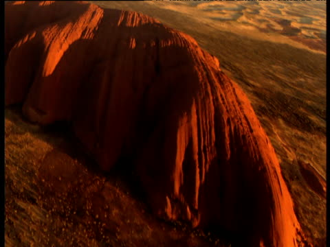 sweeping track over glowing red sandstone uluru rising out of outback, northern territory, australia - エアーズロック点の映像素材/bロール