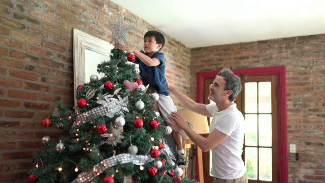 vídeos de stock e filmes b-roll de sweet argentina male couple and his son decorating the christmas tree at home - enfeitar a árvore de natal