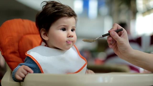vídeos de stock, filmes e b-roll de doce bebê menino comer alguns alimentos sólidos no café - comida de bebê