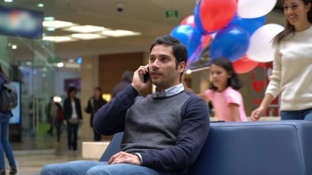 vídeos y material grabado en eventos de stock de los niños dulces y cónyuge sorprendente hombre en llamada telefónica en el centro comercial para el día del padre con globos y un presente - father day