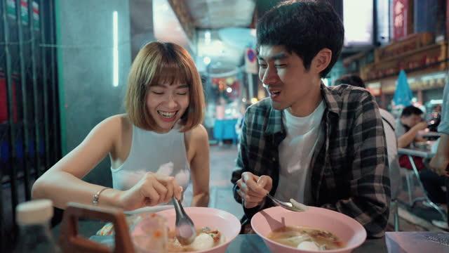 sweet couple enjoying street food at yaowarat road, bangkok - white caucasian stock videos & royalty-free footage