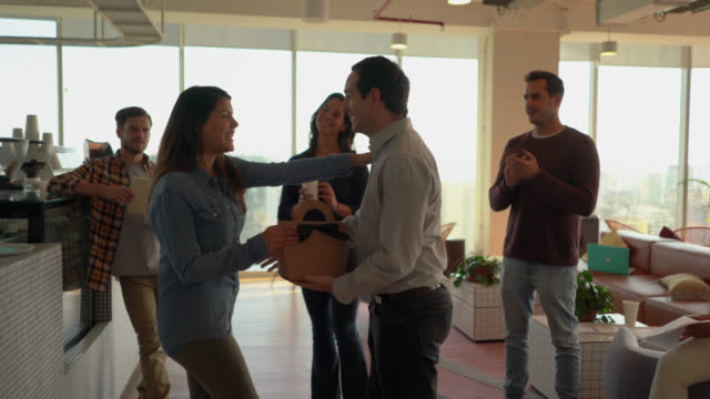sweet coworkers handing a birthday present to female colleague as she thanks each one with a hug and kiss - coworker stock videos & royalty-free footage