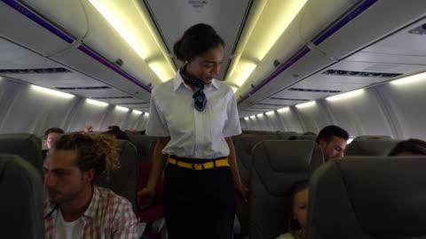 süße flugbegleiterin überprüfen, ob alle ihre sicherheitsgurte tragen und helfen, einen kleiner junge - innenaufnahme stock-videos und b-roll-filmmaterial