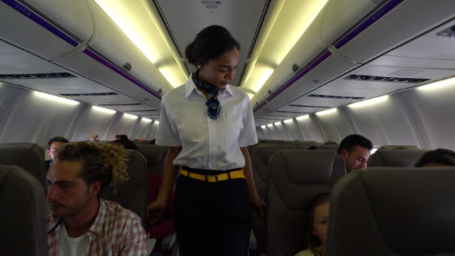 vídeos de stock e filmes b-roll de sweet flight attendant checking if everyone is wearing their seatbelts and helping a little boy - interior