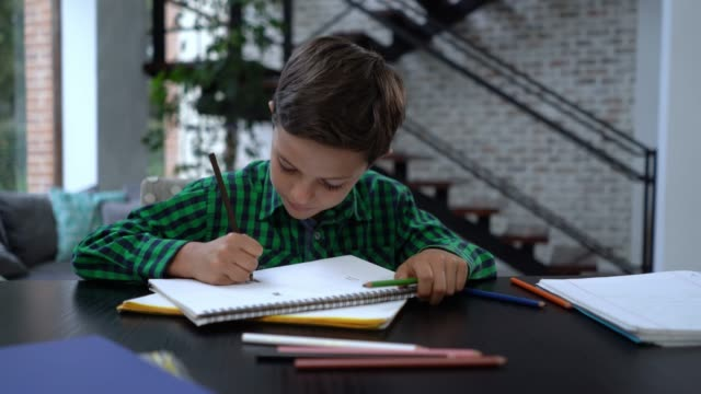 Sweet little boy at home drawing on notebooks looking very happy