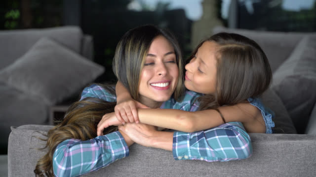 sweet little girl hugging mother and kissing her on cheek while both face camera smiling - single parent family stock videos & royalty-free footage