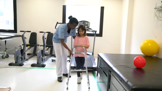 sweet little girl using a mobility walker with there help of therapist during physical therapy - crutch stock videos & royalty-free footage