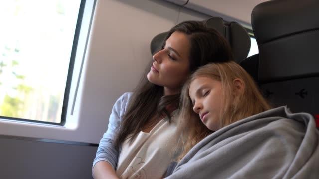 vídeos y material grabado en eventos de stock de dulce madre que cubre a su hija dormida y se inclina contra su hombro en el tren - ruso europeo oriental