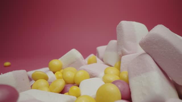 ピンクのバックラウンドで分離された甘いマシュマロとキャンディー - ジェリービーンズ点の映像素材/bロール