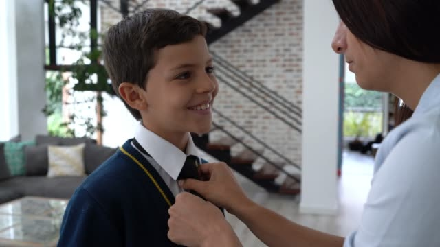 sweet mother helping son with his necktie while talking - school uniform stock videos & royalty-free footage