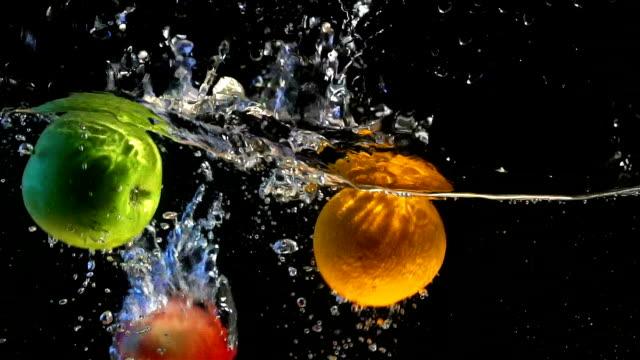 vídeos de stock e filmes b-roll de sweet orange dipping in water slow motion - maçã