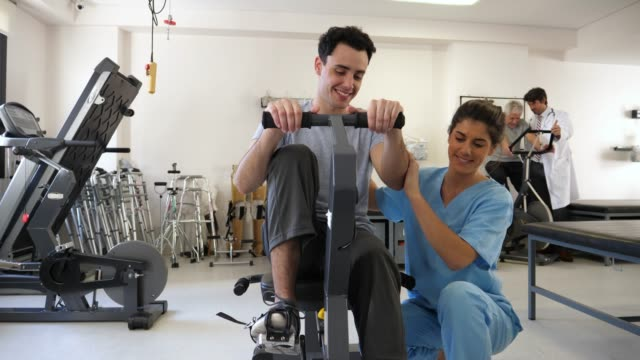 vídeos de stock e filmes b-roll de sweet physiotherapist assisting her patient while he is on a static bicycle both smiling very happy - recuperação