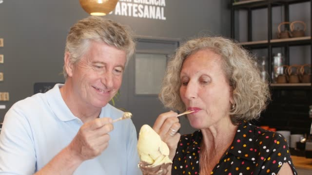 sweet senior couple sharing an ice cream at the ice cream parlor while talking - serving scoop stock videos & royalty-free footage