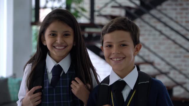 sweet siblings running towards camera while wearing their school uniform and backpack smiling - schoolgirl stock videos & royalty-free footage