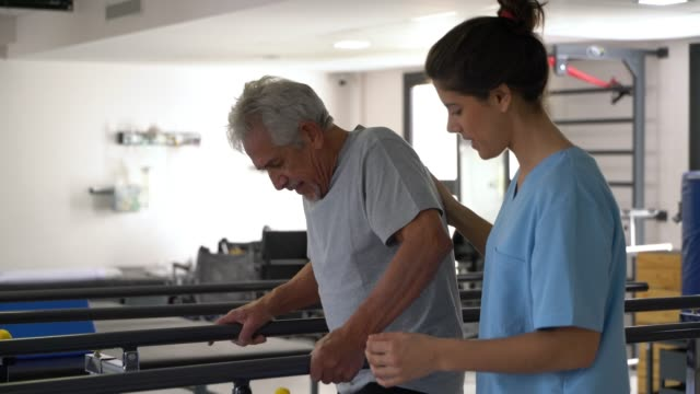 vídeos de stock e filmes b-roll de sweet therapist motivating her senior patient walk with the help of parallel bars smiling - recuperação