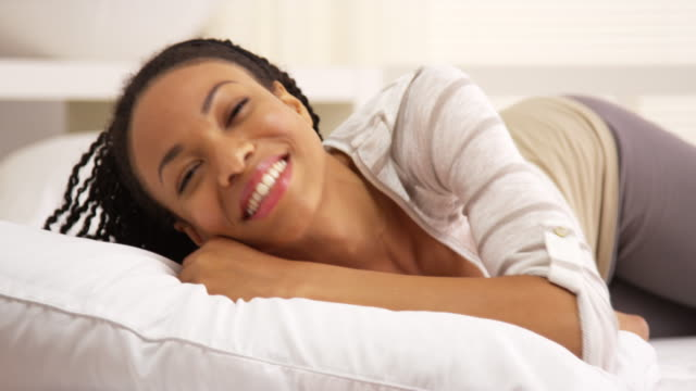 Sweet woman smiling and laughing ong bed