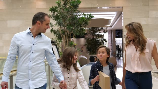 sweet young family at the mall holding hands while walking and talking very happy - shopping mall stock videos & royalty-free footage