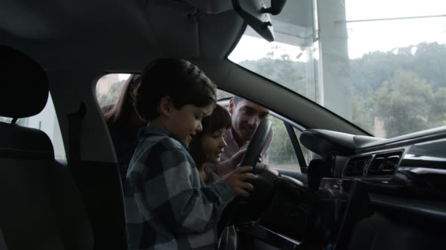 sweet young family with two children looking at the interior of a car very excited at a dealership - family with two children stock videos & royalty-free footage