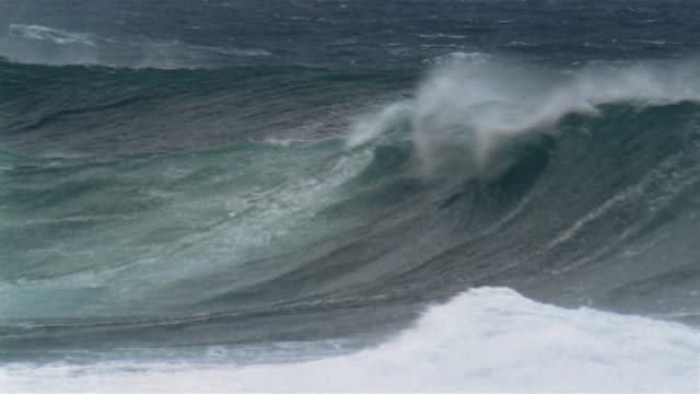 Swells breaking on beach and spitting up spray during storm / North Shore, Oahu, Hawaii