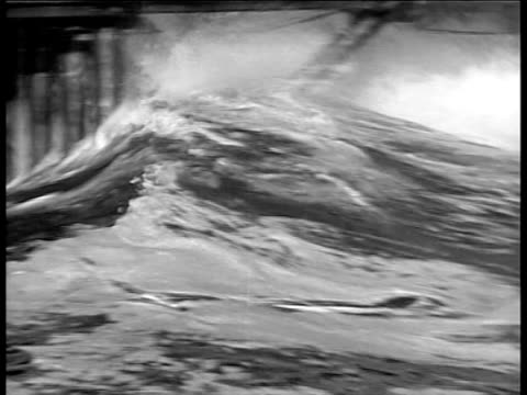 vídeos y material grabado en eventos de stock de swift wave flowing over rocks onto street, under pier / wave flowing under destroyed pier / wave flowing with debris after storm. spectacular storm... - 1934
