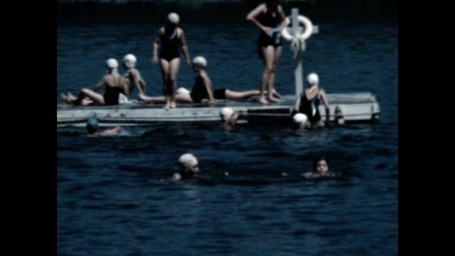 vídeos de stock, filmes e b-roll de swim at a girls camp on lake schroon in the adirondacks in the 1940's - touca de natação