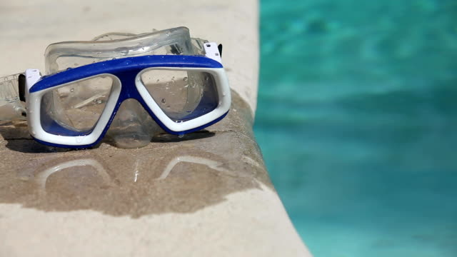 swim goggles by edge of swimming pool - pair stock videos and b-roll footage
