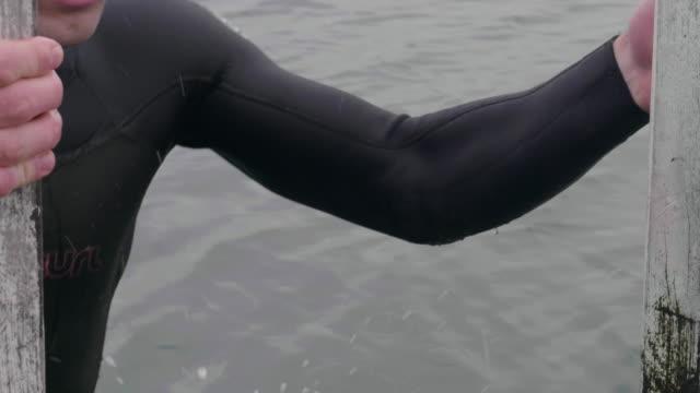 vídeos de stock, filmes e b-roll de swimmer climbing down into the water - traje de mergulho