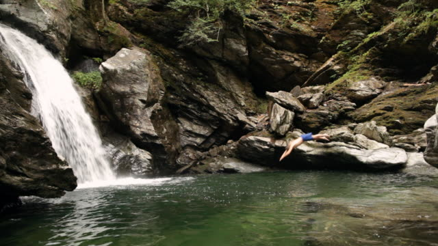 ws swimmer diving off of a rock into the river next to the waterfall / stowe, vermont, united states - vermont stock-videos und b-roll-filmmaterial