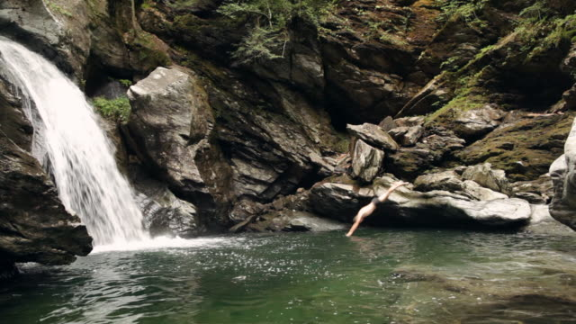 ws swimmer diving off of a rock into the river next to the waterfall / stowe, vermont, united states - newoutdoors stock videos & royalty-free footage
