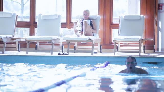 stockvideo's en b-roll-footage met  pan swimmer doing laps after talking woman sitting / stowe, vermont, united states - eendelig zwempak