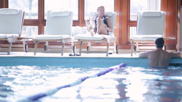 ws swimmer doing laps resting on pool edge to talk to friend / stowe, vermont, united states - rand stock-videos und b-roll-filmmaterial