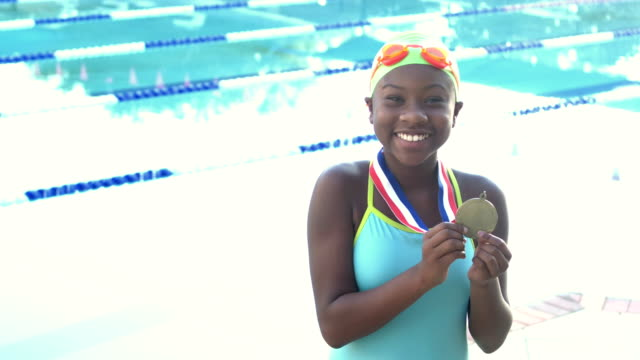 swimmer holding up medal for winning race - swimming cap stock videos & royalty-free footage