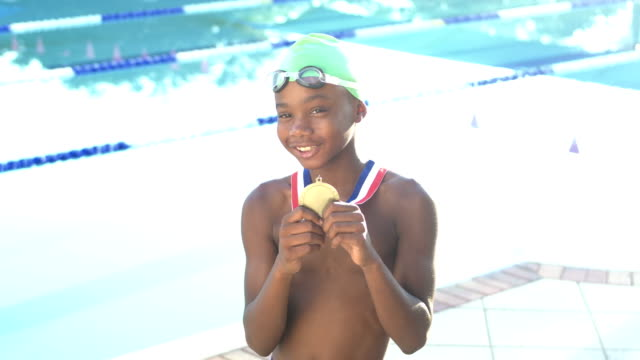 swimmer holding up medal for winning race - competitive sport stock videos & royalty-free footage