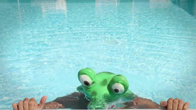 vidéos et rushes de natation dans un costume de grenouille ressortent de l'eau - se déguiser