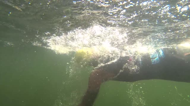 Swimmer in SOS Triathlon underwater camera surfaces and goes back under