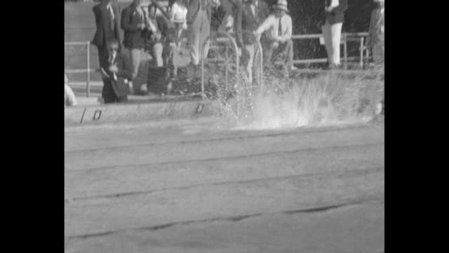 Swimmer on far side of pool relay at Summer Olympics at Los Angeles Swimming Stadium / wide shot of pool / slow motion of swimmer / woman swimmer on...