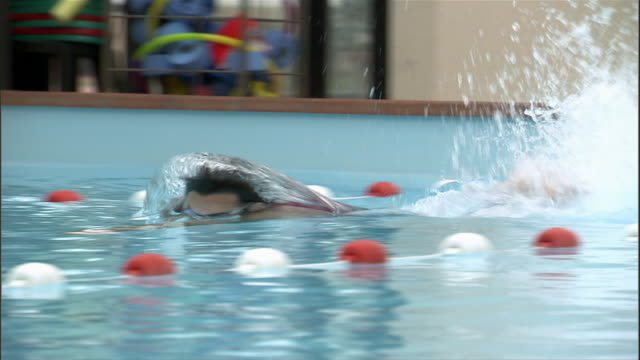 Swimmer pushing off from wall / panning swimming across pool / tilt up to trainer walking alongside pool shouting encouragement