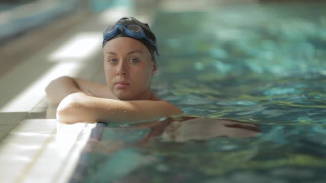 vídeos de stock, filmes e b-roll de sv swimmer resting on side of pool / vancouver, british columbia, canada - touca de natação