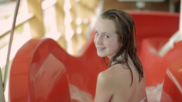 pan swimmer sliding down water slide / vancouver, british columbia, canada - nur weibliche teenager stock-videos und b-roll-filmmaterial