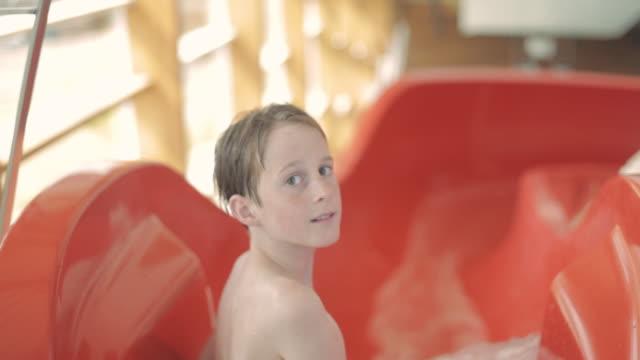 stockvideo's en b-roll-footage met pan swimmer sliding down water slide / vancouver, british columbia, canada - alleen jongens