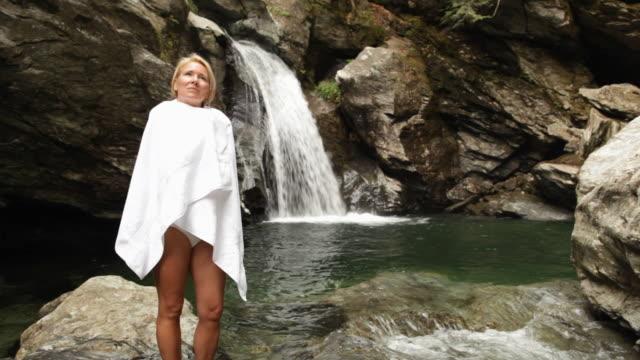 ws swimmer standing in front of waterfall / stowe, vermont, united states - タオルにくるまる点の映像素材/bロール
