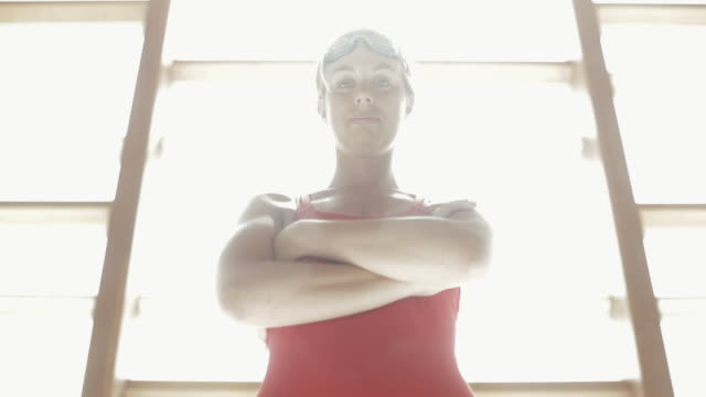 tu swimmer standing with arms crossed and goggles on head / vancouver, british columbia, canada - one piece swimsuit stock videos and b-roll footage