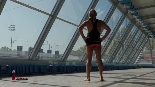 vídeos de stock e filmes b-roll de swimmer warming up before entering the pool - dor no pescoço