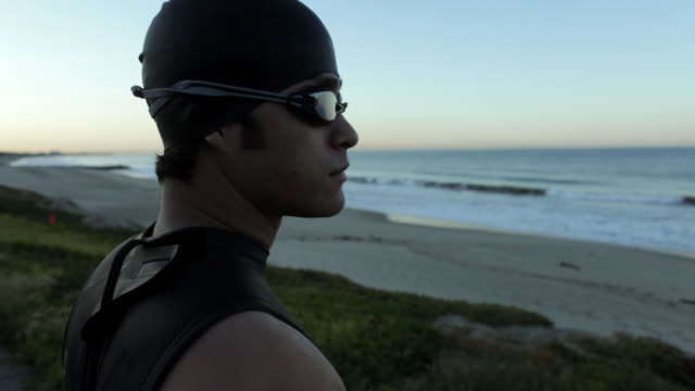 cu swimmer wearing cap and goggles standing on beach and looking at ocean / los angeles, california, usa - asian and pacific islander stock videos & royalty-free footage