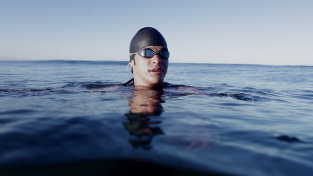 MS ZO Swimmer wearing cap and goggles treading water in ocean / Los Angeles, California, USA