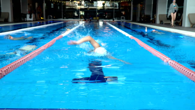 swimmer woman swimming into camera - freestyle swimming stock videos and b-roll footage