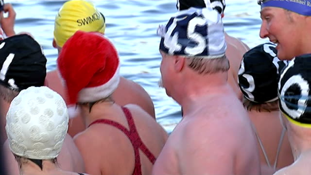 swimmers around the world take traditional christmas dips england london hyde park serpentine swimmers standing in swimming costumes in line by... - swimming costume stock videos and b-roll footage