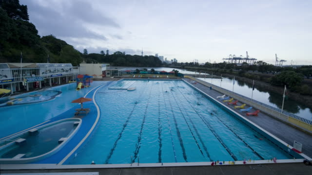 HA WS TL Swimmers arriving to swim laps at pool as dawn turns to day/ Auckland, New Zealand