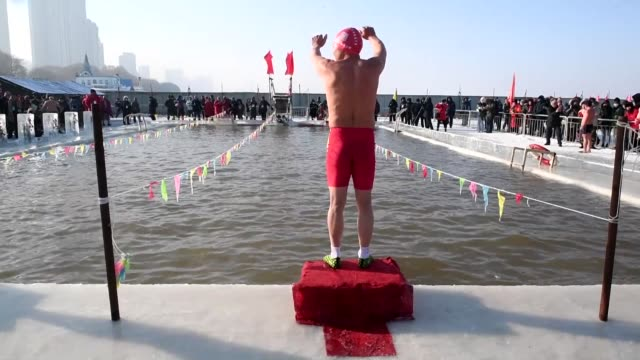 swimmers compete in an ice swimming contest in a pool carved from the frozen ice of the songhua river during the annual harbin ice and snow festival... - schneefestival stock-videos und b-roll-filmmaterial